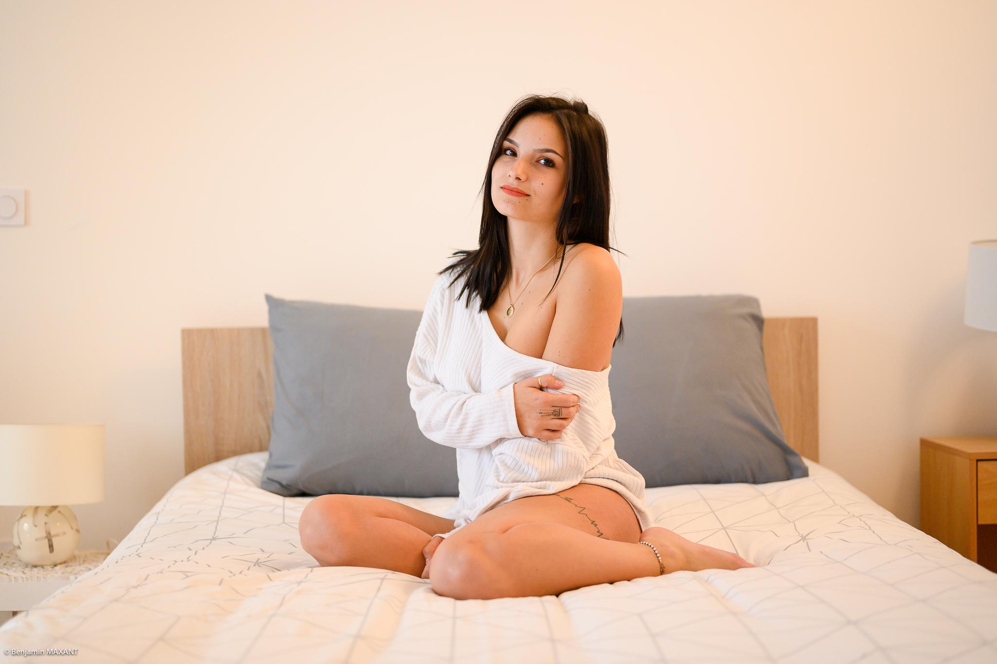Séance photo boudoir ensemble blanc souple ouvert modèle assise sur le lit