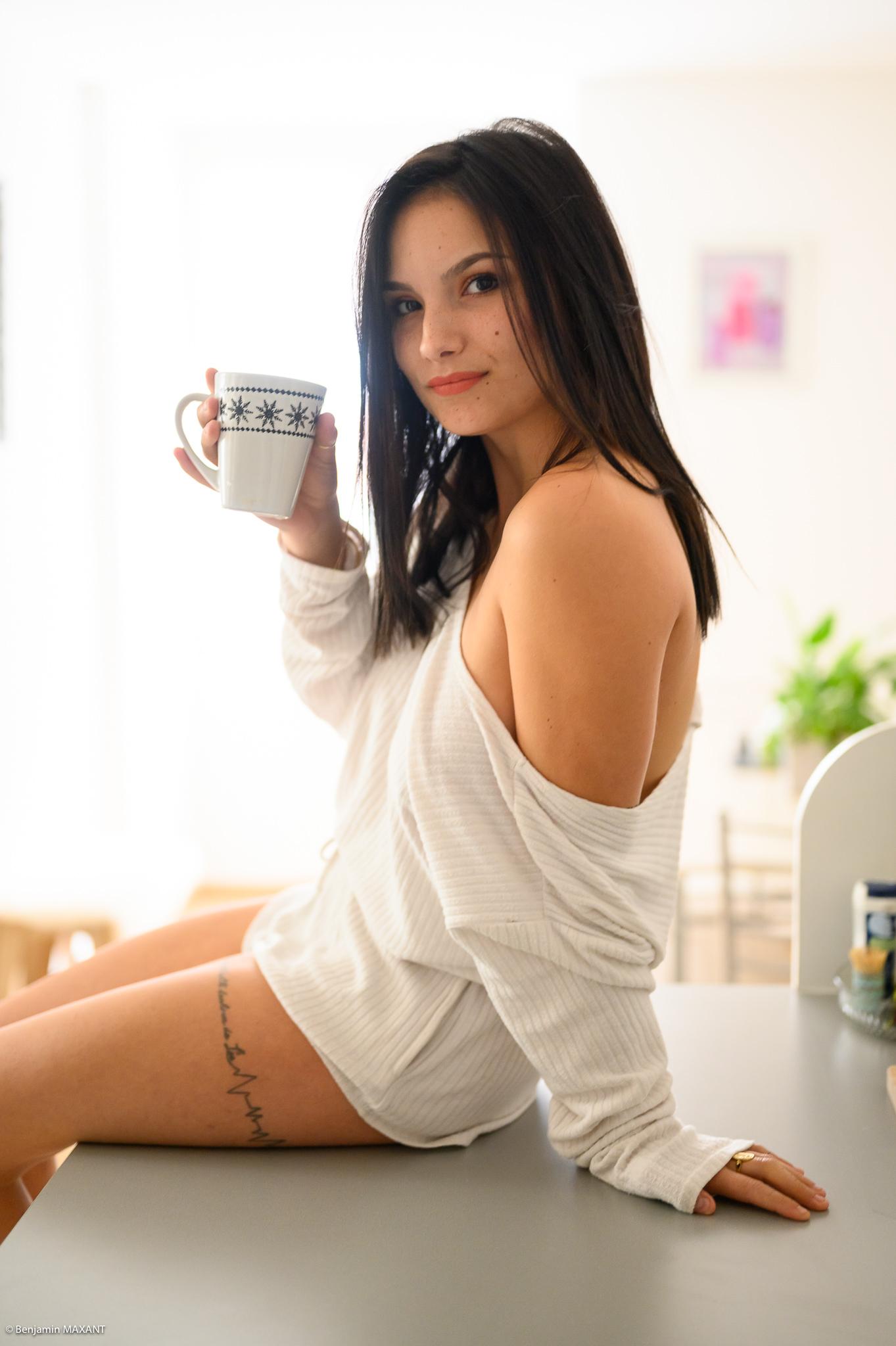 Séance photo boudoir ensemble blanc souple assise sur le plan de travail avec un mug