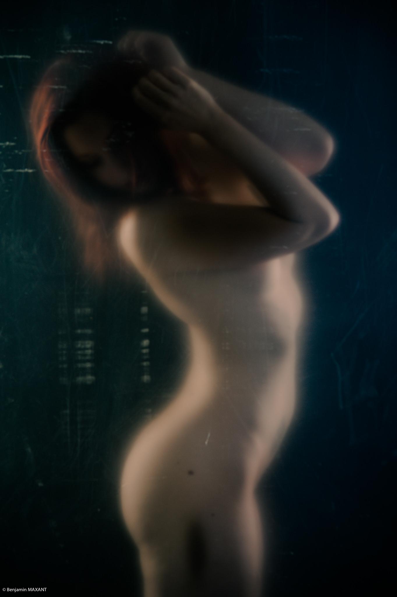 Séance photo nu artistique avec une modèle placée derrrière une plaque en plastique transparente
