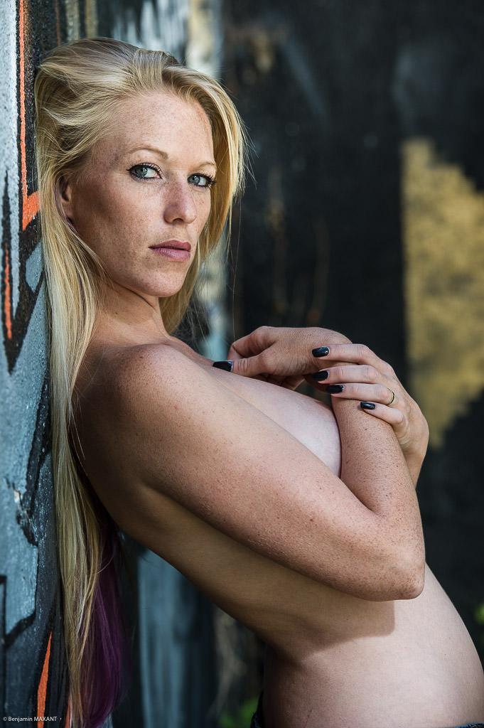 Séance photo nu en extérieur femme adossée à un mur cache ses seins
