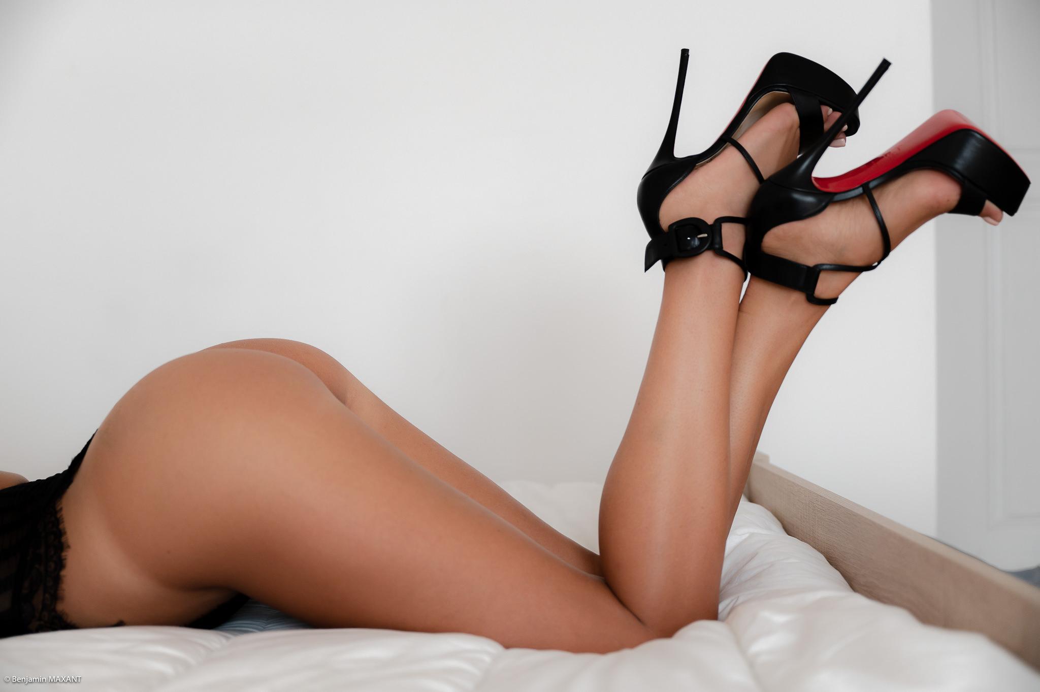 Séance photo érotique Christelle body noir allongée lit cambrée fesses louboutin