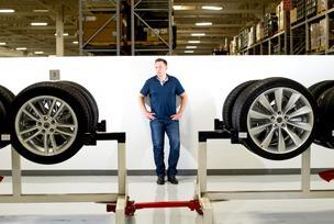 CEO Elon Musk stands with Model S wheels at Tesla's plant in Fremont, Calif.