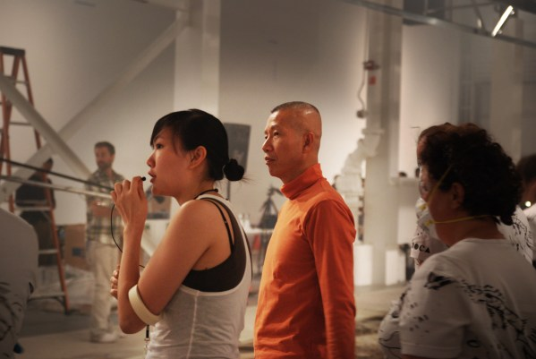 caption: Cai Guo-Qiang and Kelly from Cai Studio organize the volunteers.  photo by Russell Bates