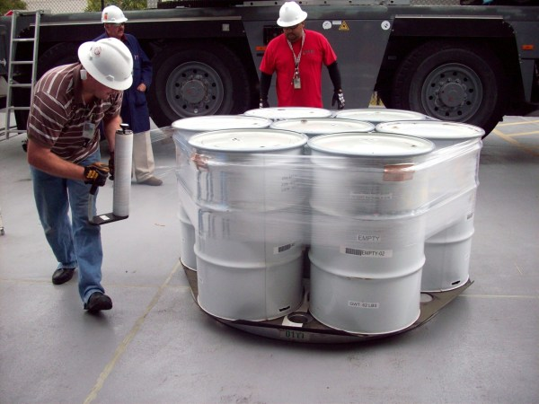 """""""Operators prepare drums of contact-handled transuranic waste for loading into transportation containers,"""" headed for WIPP. Image: US Department of Energy."""