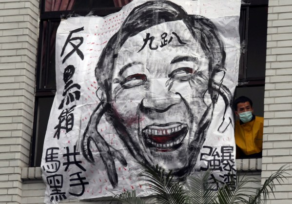 """A protester looks out from a window next to a cartoon depicting Taiwan's President Ma Ying-jeou at Taiwan's legislature in Taipei, March 21, 2014. The Chinese characters on the cartoon read, """"Anti-black box"""" (top, L), """"Communist Ma the black hand"""" (bottom, L), """"Rape Taiwan"""" (R) and """"Nine percent approval rating""""  Photo: Reuters/Patrick Lin."""