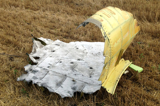 """A piece of wreckage from the Malaysia Airlines jet downed over eastern Ukraine last week shows damage, including shrapnel holes and blistered paint, that is consistent with a hit from a fragmenting warhead, according to consultants with IHS-Jane's."" Photo: Noah Sneider, via NYT"