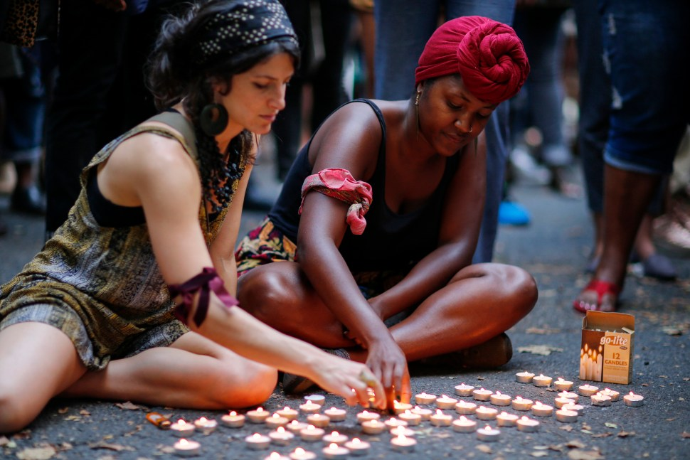 Women light candles while attending a vigil to honor Michael Brown