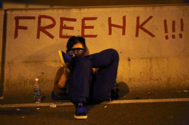 A protester sits as he blocks the main street to the financial Central district outside the government headquarters in Hong Kong September 29, 2014.  [REUTERS/Carlos Barria]