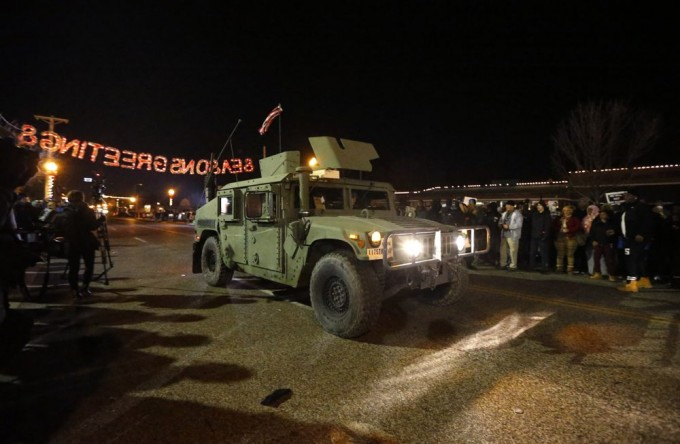 A Humvee moves on the street between protestors and police in front of the Ferguson Police Department, in Ferguson, Missouri, November 25, 2014. United Nations Secretary-General Ban Ki-moon on Tuesday urged protesters in Ferguson, Missouri, and elsewhere in the United States to refrain from violence and called on law enforcement to protect the rights of people to demonstrate peacefully.   REUTERS/Jim Young