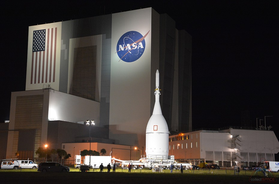The Exploration Flight Test-1 (EFT-1) Orion rolls past the Vehicle Assembly Building at Kennedy Space Center. (collectSPACE)