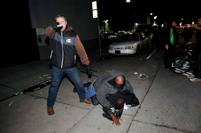 An undercover police officer who had been marching with anti-police demonstrators, aims his gun at protesters after some in the crowd attacked him and his partner in Oakland, California December 10, 2014.  Photo: REUTERS/Noah Berger