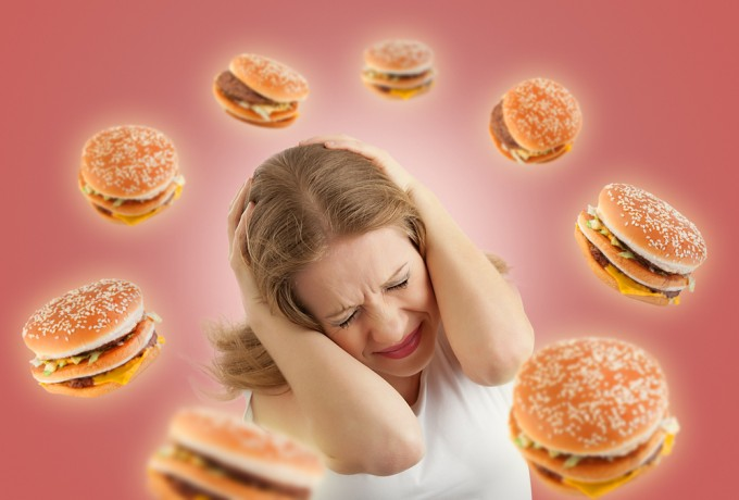 """Photo: """"Diet concept. frightened girl in the stress and flying around the burgers on a red background."""" Evgeny Atamanenko for Shutterstock."""