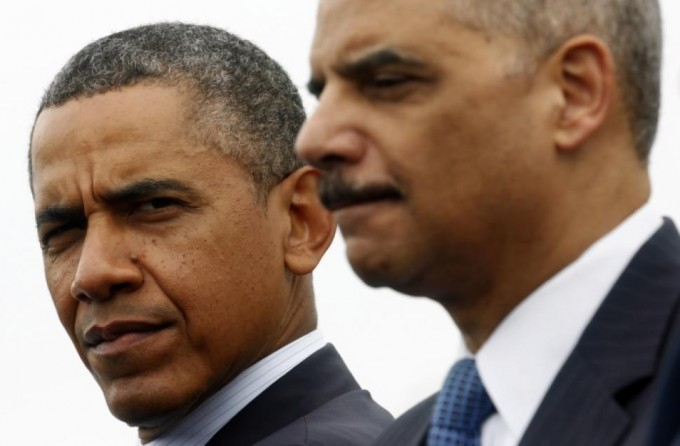 U.S. President Barack Obama looks toward Attorney General Eric Holder. Justice Department investigators have engaged in aggressive tactics against journalists in recent months. [Reuters]