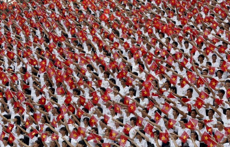 Students wave Vietnamese national flags during a military parade as part of the 40th anniversary of the fall of Saigon in Ho Chi Minh City (formerly Saigon), Vietnam, April 30, 2015. Vietnam refers to the event as the date of its reunification. REUTERS/Kham