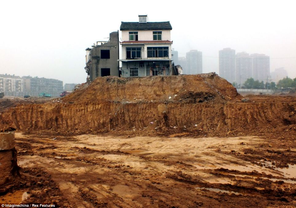Two homes on a construction site in Yichang, Hubei province, China, have become 'nail' houses after being left isolated when buildings surrounding them were torn down