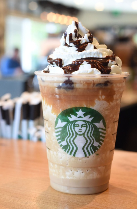 Caramel Cocoa Cluster Toffee Nut Syrup Coffee Milk And Ice Topped With A Layer Of Dark Sauce Finished Whipped Cream Drizzle