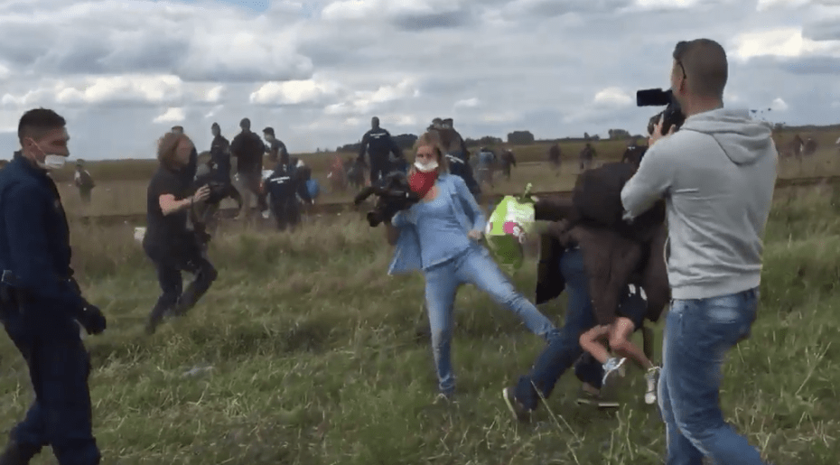 A camerawoman for the Hungarian broadcaster N1TV tripped a man with a child in his arms who was fleeing from police at a migrant camp near the Serbian border on Tuesday. Credit Stephan Richter, via Twitter