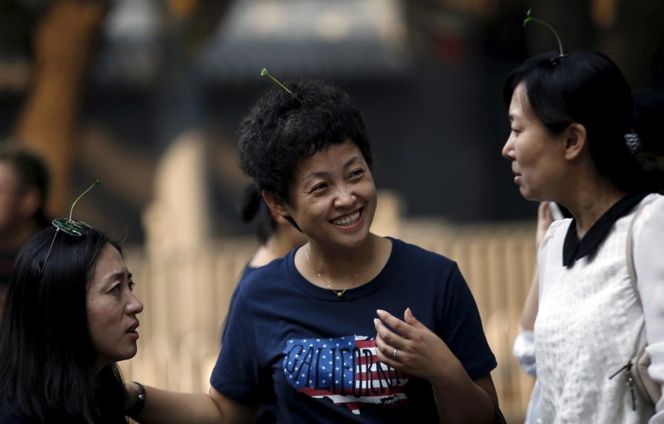 Women wearing sprouts-like hairpins chat in Beijing [REUTERS]