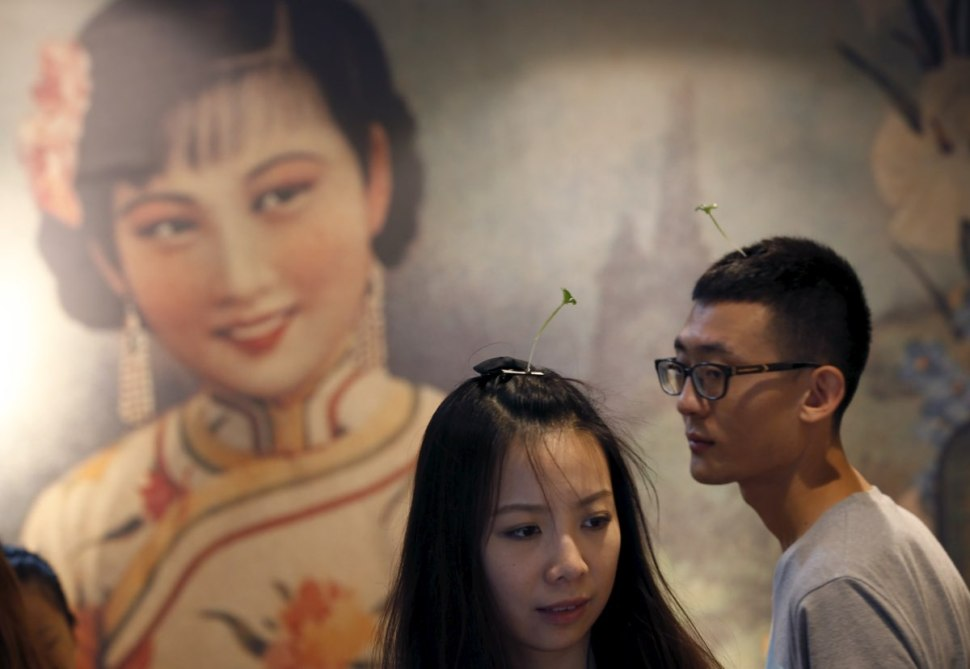A couple wearing sprout-like hairpins look around a Beijing shop. REUTERS