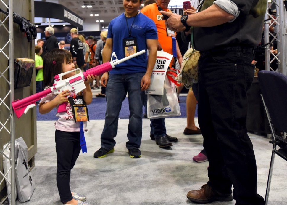 A young NRA member, gets her photo with a non-toy rifle  at an NRA convention [REUTERS]