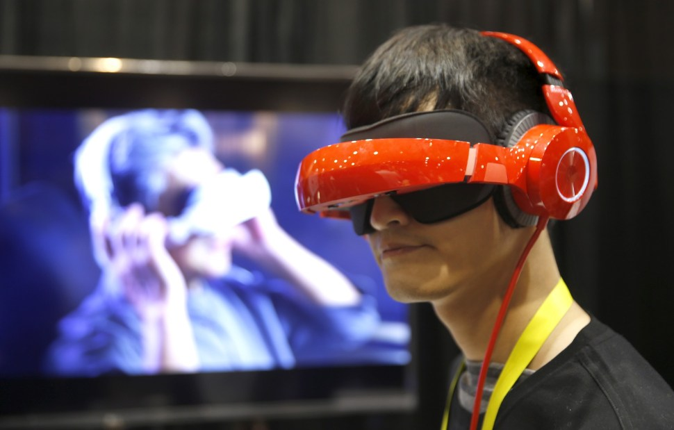 Eric Yu of Royole models the company's foldable Smart Mobile Theater system. The $700.00 system has noise-canceling headphones and a viewing system that is vision correctable so you don't need to wear your glasses, Yu said.  REUTERS