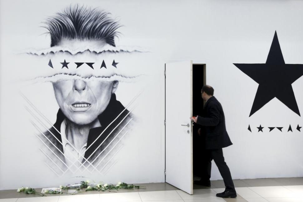 A man enters an office beside a large drawing by Belgian artist Lucien Gilson of David Bowie in a shopping mall in Brussels