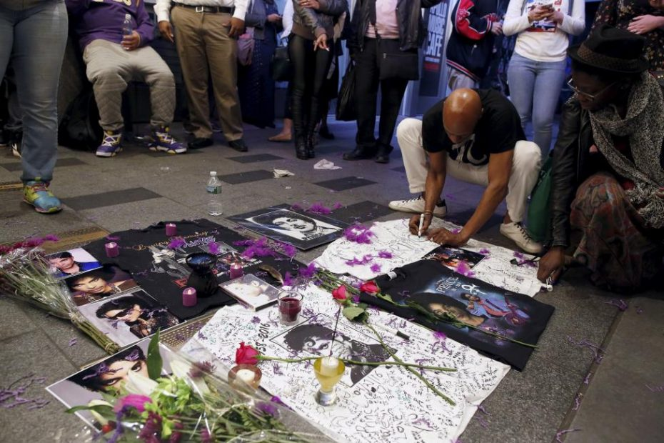 A man writes on a makeshift memorial as fans gather at Harlem's Apollo Theater to celebrate the life of Prince in Manhattan. [REUTERS/Andrew Kelly]