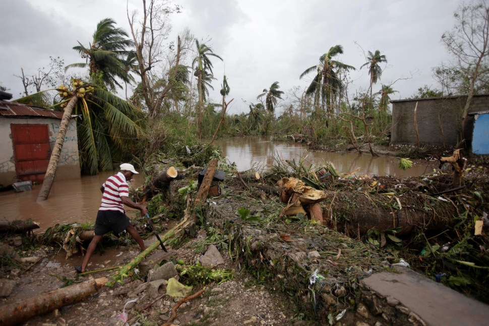 A man cuts branches off fallen trees in a flooded area by a river after Hurricane Matthew in Les Cayes, Haiti, October 5, 2016. REUTERS/Andres Martinez Casares - RTSQVTS