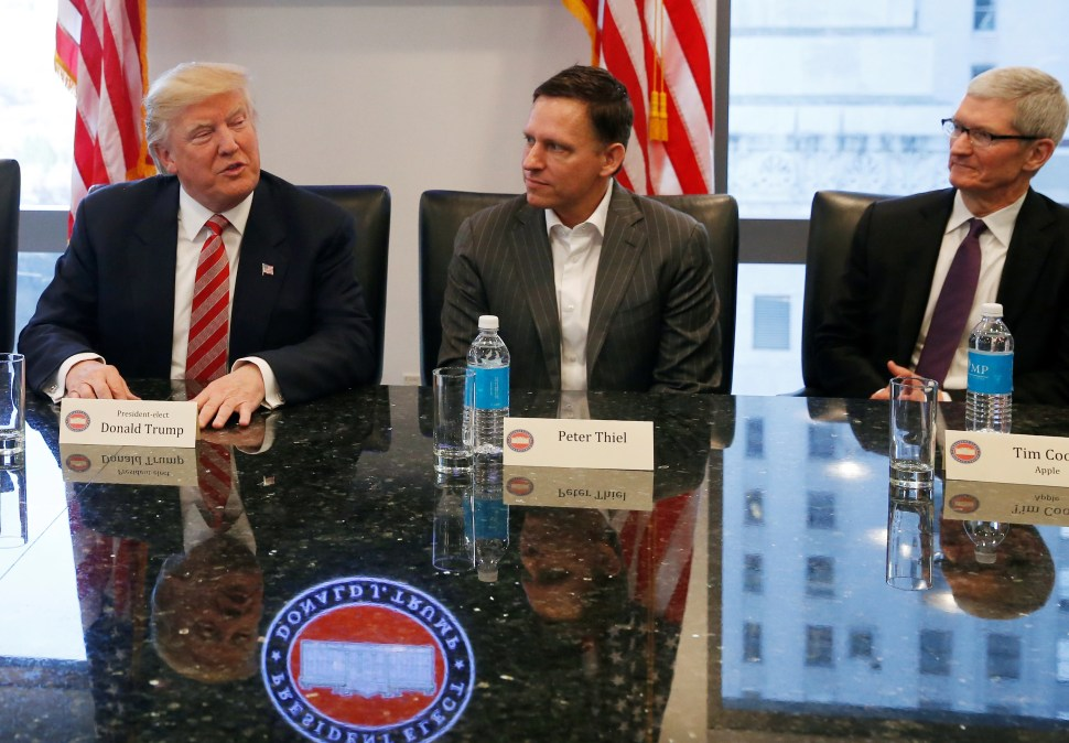 Trump speaks while PayPal co-founder and Facebook board member Peter Thiel and Apple Inc CEO Tim Cook look on during a meeting with technology leaders at Trump Tower in New York U.S., December 14, 2016. REUTERS