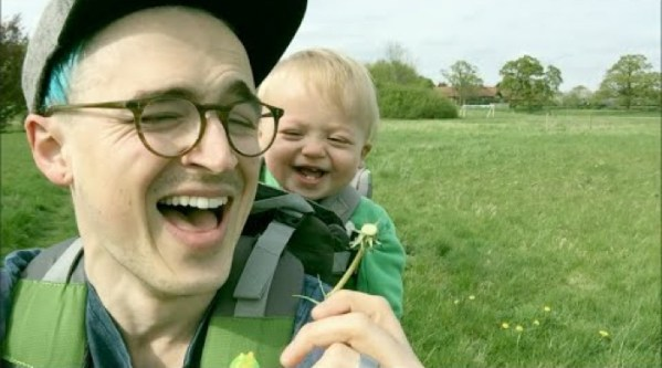 Baby with contagious giggle can't stop laughing at dad blowing dandelion flowers