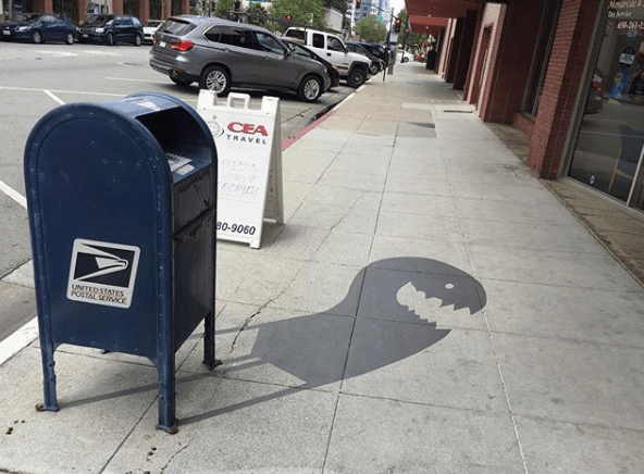 Artist paints playful shadow art on sidewalks