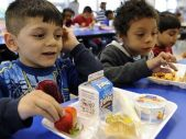 In this April 29, 2014 file photo, two elementary school boys, ages 5 and 6, eat lunch