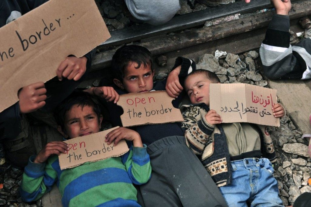 "TOPSHOT - Children lie on railway track as they hold banners reading ""Open the border"" during a demonstration near the makeshift camp close to the Greek village of Idomeni by the Greek-Macedonian border where thousands of refugees and migrants are trapped by the Balkan border blockade, on March 12, 2016. Greece aims to deal swiftly with the migrant overflow at the Idomeni refugee camp on the Greek-Macedonian border where some 12,000 people are camping in miserable conditions waiting to cross. Conditions in the camp have worsened since four Balkan countries shut their borders on March 8 and 9, closing off the main route to wealthy northern Europe trodden by hundreds of thousands of migrants in the last two years. / AFP / SAKIS MITROLIDIS (Photo credit should read SAKIS MITROLIDIS/AFP/Getty Images)"