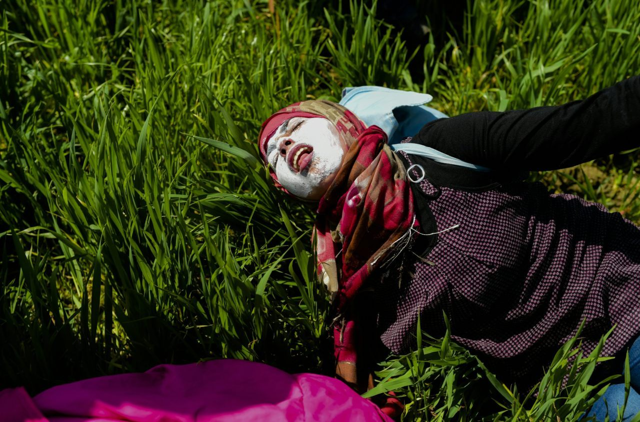A woman with toothpaste smeared over her face to protect her from teargas, lies on the ground (BULENT KILIC/AFP/Getty Images)