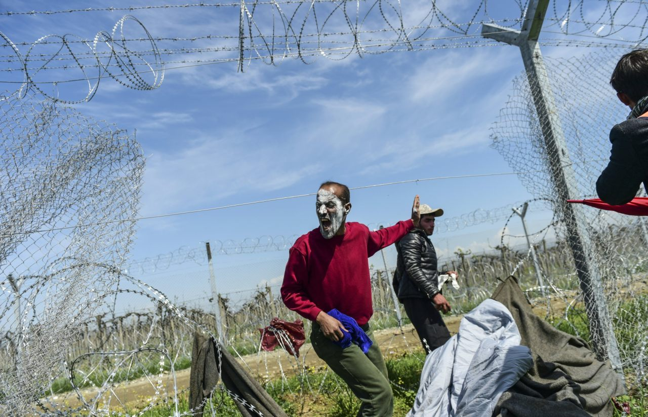 A man calls to other migrants to walk through the torn down wire fencing along the border into Macedonia (BULENT KILIC/AFP/Getty Images)