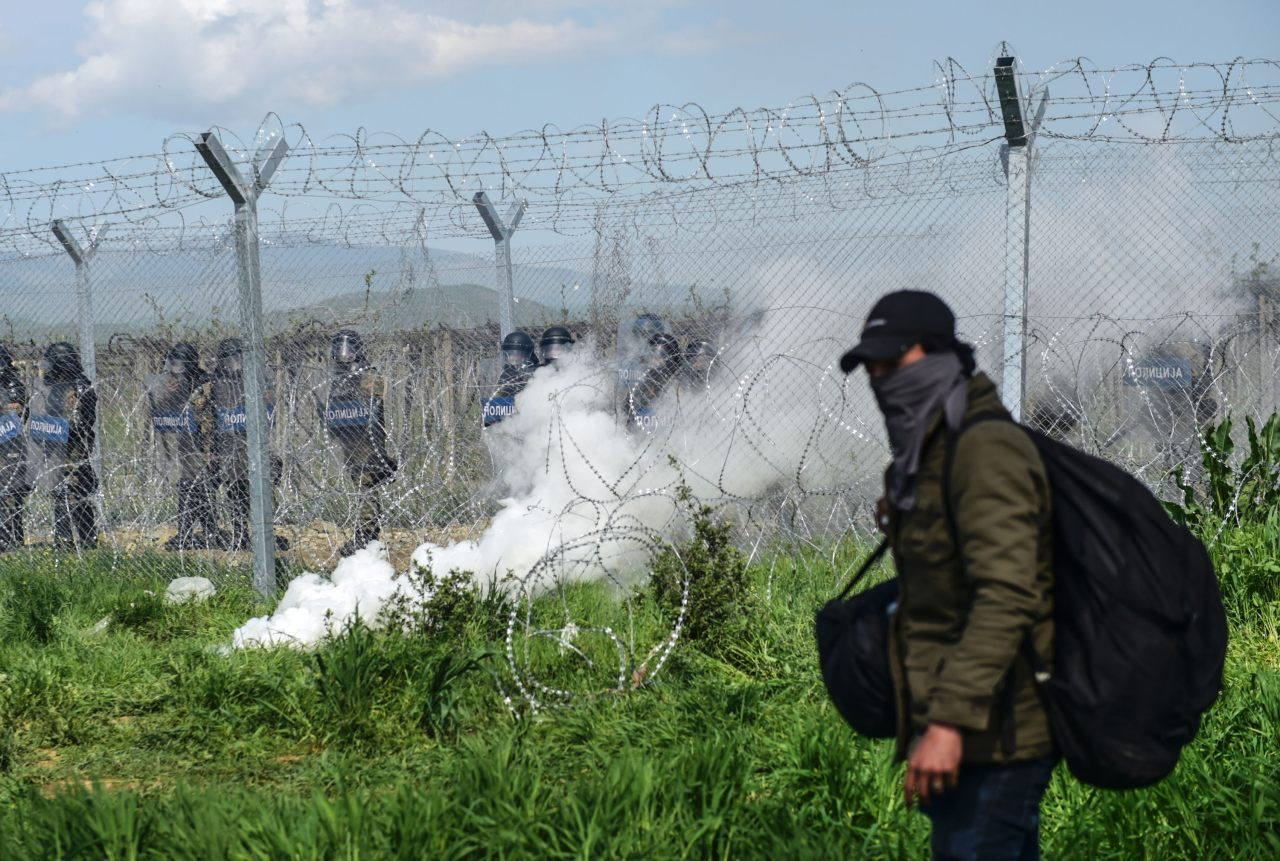 Migrants and refugees head back to the Greek side during clashes with Macedonian soldiers near their makeshift camp in the northern Greek border village of Idomeni, on April 10, 2016. Dozens of people were hurt when police fired tear gas on a group of migrants as they tried to break through a fence on the Greece-Macedonia border, the medical charity Doctors without Borders (MSF) said. A plan to send back migrants from Greece to Turkey sparked demonstrations by local residents in both countries days before the deal brokered by the European Union is set to be implemented. / AFP / BULENT KILIC (Photo credit should read BULENT KILIC/AFP/Getty Images)
