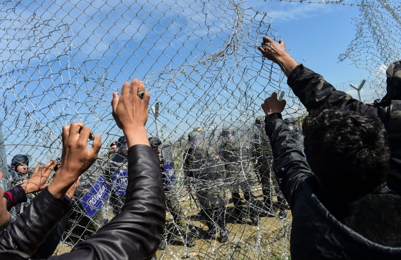 Migrants try to tear down the border fence as Macedonian police watch from the other side (BULENT KILIC/AFP/Getty Images)