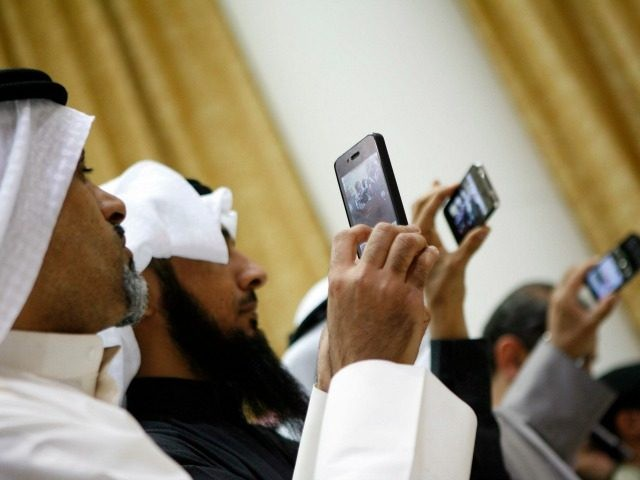 Kuwaitis use their mobile phone to follow the press conference for Kuwaiti MP's after the end of the Kuwaiti PM grilling session at the Kuwait's National Assembly in Kuwait City on December 28, 2010.