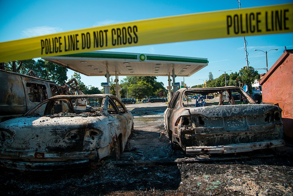 MILWAUKEE, WI - AUGUST 14: Cars stand burned in the lot of the BP gas station after rioters clashed with the Milwaukee Police Department protesting an officer involved killing August 14, 2016 in Milwaukee, Wisconsin. Hundreds of angry people confronted police after an officer shot and killed a fleeing armed man earlier in the day. (Photo by Darren Hauck/Getty Images)