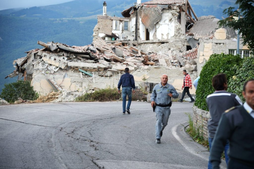 Victims and rescuers walk among the rubble of houses after a strong heartquake hit Amatrice on August 24, 2016. Central Italy was struck by a powerful, 6.2-magnitude earthquake in the early hours, which has killed at least three people and devastated dozens of mountain villages. Numerous buildings had collapsed in communities close to the epicenter of the quake near the town of Norcia in the region of Umbria, witnesses told Italian media, with an increase in the death toll highly likely. / AFP / FILIPPO MONTEFORTE (Photo credit should read FILIPPO MONTEFORTE/AFP/Getty Images)