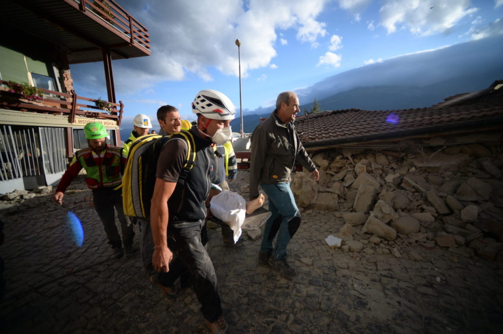 Rescuers carry an injured man among damaged homes after a strong heathquake hit Amatrice on August 24, 2016. Central Italy was struck by a powerful, 6.2-magnitude earthquake in the early hours, which has killed at least three people and devastated dozens of mountain villages. Numerous buildings had collapsed in communities close to the epicenter of the quake near the town of Norcia in the region of Umbria, witnesses told Italian media, with an increase in the death toll highly likely. / AFP / FILIPPO MONTEFORTE (Photo credit should read FILIPPO MONTEFORTE/AFP/Getty Images)