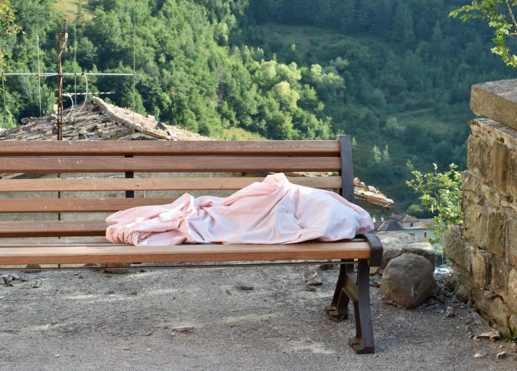 ARQUATA DEL TRONTO, ITALY - AUGUST 24: The body of an unidentifeid child lies on a bench on August 24, 2016 in Arquata del Tronto, Italy. Central Italy was struck by a powerful, 6.2-magnitude earthquake in the early hours, which has killed at least thirteen people and devastated dozens of mountain villages. Numerous buildings have collapsed in communities close to the epicenter of the quake near the town of Norcia in the region of Umbria, witnesses have told Italian media, with an increase in the death toll highly likely (Photo by Giuseppe Bellini/Getty Images)