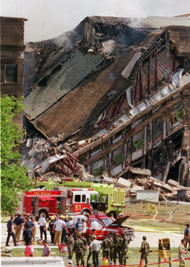 Rescue worker look over damage at the Pentagon Tuesday, Sept. 11, 2001. The Pentagon burst into flames and a portion of one side of the five-sided structure collapsed after the building was hit by an aircraft in an apparent terrorist attack. (AP Photo/Kamneko Pajic)