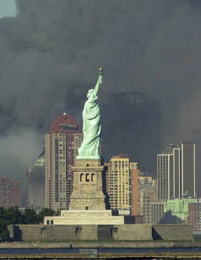 Thick smoke billows into the sky from the area behind the Statue of Liberty where the World Trade Center towers stood Tuesday, Sept. 11, 2001. The towers collapsed after terrorists crashed two planes into them Tuesday. (AP Photo/Daniel Hulshizer)