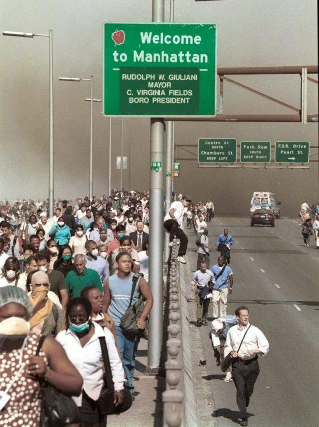 People flee lower Manhattan across the Brooklyn Bridge in New York, Tuesday, Sept. 11, 2001, following a terrorist attack on the World Trade Center. (AP Photo/Daniel Shanken) MANDATORY CREDIT