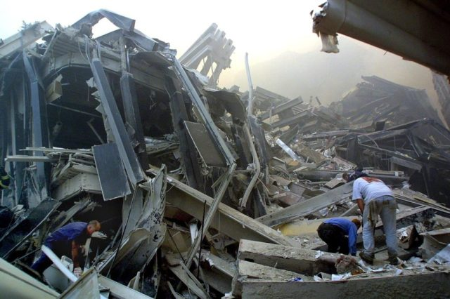 Rescue workers make their way through the rubble of the World Trade Center 11 September 2001 in New York after two hijacked planes flew into the landmark skyscrapers. AFP PHOTO/Doug KANTER (Photo credit should read DOUG KANTER/AFP/Getty Images)