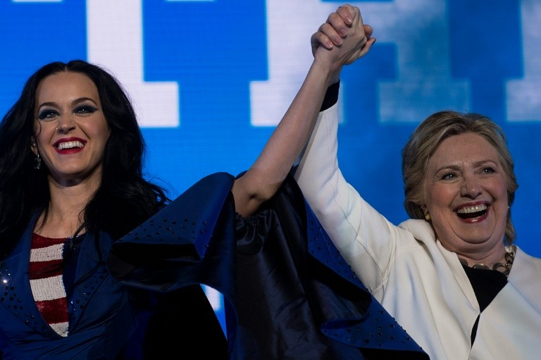 Singer Katy Perry (L) and Democratic presidential nominee Hillary Clinton cheer during a GOTV concert in Philadelphia, Pennsylvania