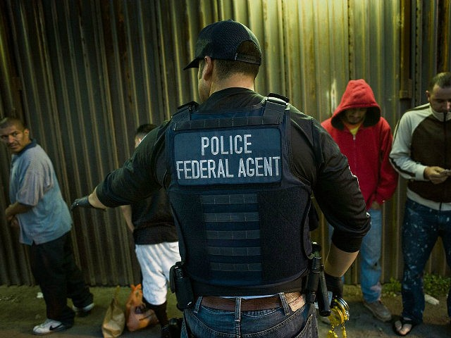 A U.S. Immigration and Customs Enforcement (ICE) agent directs a group of undocumented men being deported to Mexico at the U.S.-Mexico border in San Diego, California, U.S., on Thursday, Feb. 26, 2015. The U.S. Department of Homeland Security is nearing a partial shutdown as the agency's funding is set to expire Friday -- something Senate Majority Leader Mitch McConnell had said wouldn't happen on his watch. Photographer: David Maung/Bloomberg via Getty Images