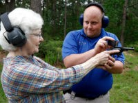 In this April 30, 2016 photograph, Jake Driskell, a Laurel police officer and owner of Gun Guy Tactical, helps Crestview Baptist Church member and first time shooter Katherine Huffman, line up her sights with her husband's revolver during the live fire portion of a enhanced concealed carry class sponsored by the church for members and area residents in Petal, Miss. The 20 participants received hands on assistance during a practical shooting exercise, a thorough review on the fundamentals of safe handling of firearms in addition to a review of the basic and enhanced Mississippi Concealed Carry laws. (AP Photo/Rogelio V. Solis)