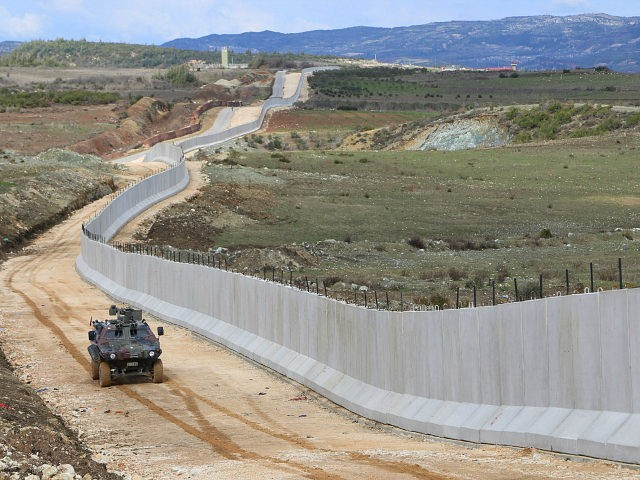HATAY, TURKEY - FEBRUARY 22: Turkish security forces patrol with an armored vehicle as 35 kilometres long, 3 metres high and 7 tones weighted concrete wall, builded in order to prevent illegal border crossing and smuggling, is seen on the Turkey - Syria border, in Hatay, Turkey on February 22, 2016. The border is guarded 24 hours a day with armored vehicles and work has begun to extend 'concrete block' to 72 kilometres by April. (Photo by Cem Genco/Anadolu Agency/Getty Images)